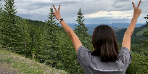 womain from the rear holding peace signs in the mountains